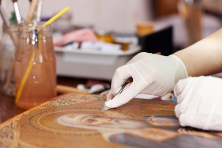 restorer cleaning ancient icon with spatula at restoration workshop photo