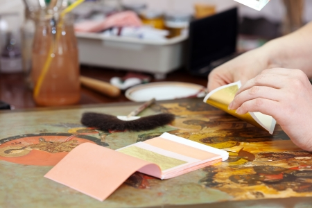 gilding: Restorer gilding on the old icon with gold leaf Stock Photo