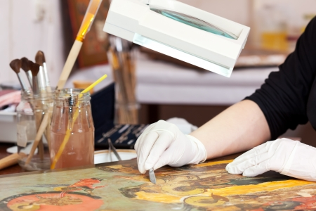 Restorer working on the ancient Christian icon with magnifying at restoration workshop photo