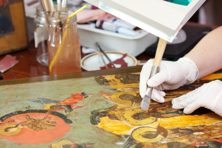 Restorer gilding on the Christian icon with agate burnisher at restoration workshop photo