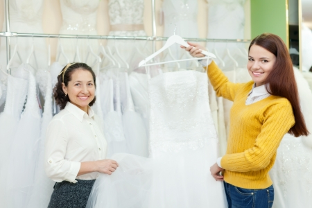 bridal gown: assistant  helps the bride in choosing bridal gown at shop of wedding fashion