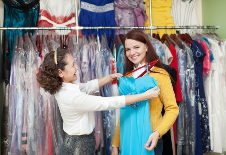 Young woman chooses evening dress at clothing shop. Friendly shop consultant helps her photo