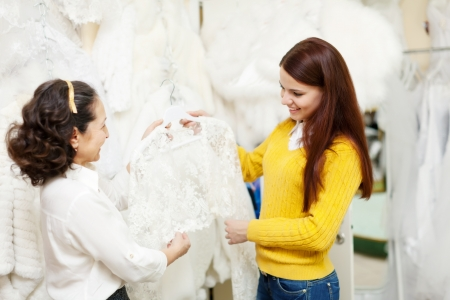 consultant helps bride chooses bridal clothes at shop of wedding fashion. Focus on girl photo