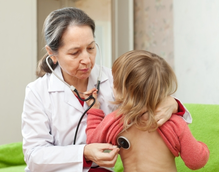 children's doctor:  mature pediatrician doctor examining child with  stethoscope. Focus on woman