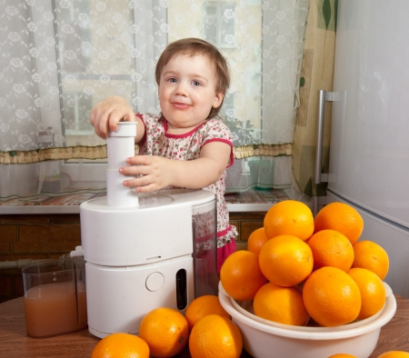 Baby girl adding orange to juicer in home kitchen photo