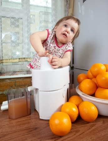 Baby girl making fresh orange juice in home kitchen photo