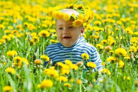 Little baby in flowers chaplet in meadow photo