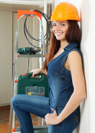 Happy  female builder in overalls and hardhat at home photo