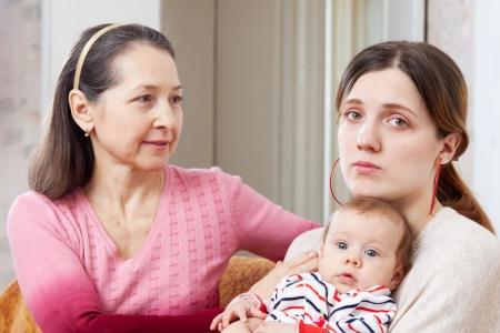 problemas familiares: Mujer madura consuela a su hija adulta triste con el beb� en casa