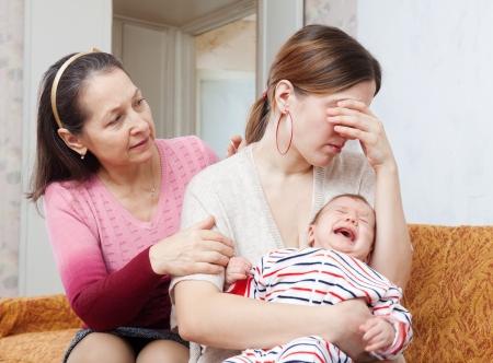 baby huilen: Rijpe vrouw geeft troost voor huilende volwassen dochter met baby thuis