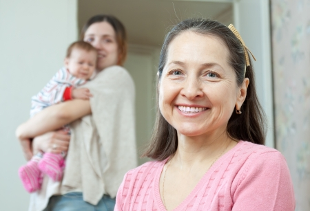 Portrait of happy mature woman with  young mother with little baby on background Stock Photo - 17592537