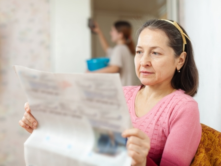 mature woman reads newspaper during girl cleans at home photo