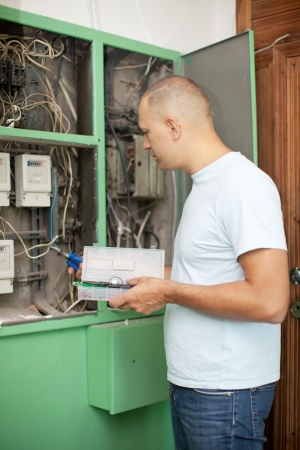 Man working with electric box at house photo