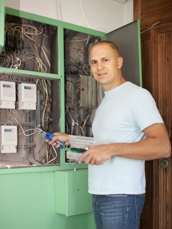 electrician works with electric box at house photo