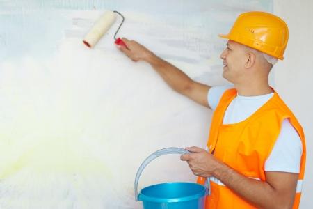 pintor de casas: pintores masculinos de la casa con el rodillo de pintura en la nueva casa