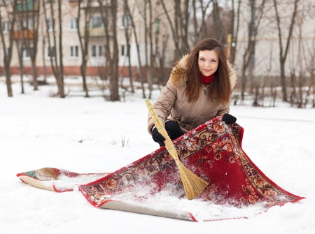 Smiling girl cleans carpet with snow in winter   photo