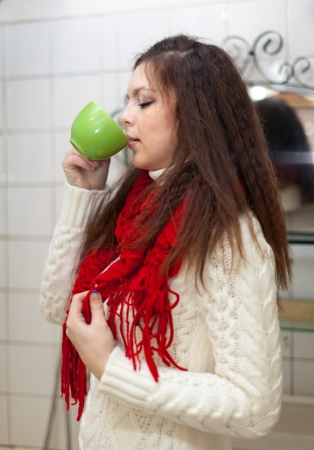 sicken: Colds woman with cup of  medicine gargling at bathroom