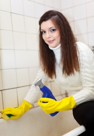 Smiling woman cleans bathroom with sponge at her home photo