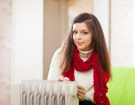 Long-haired woman near oil heater in home Stock Photo - 17642196