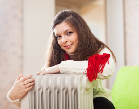 woman  warms near warm heater  in home Stock Photo - 17642194