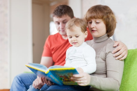 Happy parents with child looks the book in home interior Stock Photo - 17642294