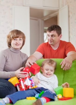 Portrait of family of three in home photo