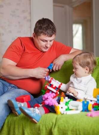 father and  three-year child plays with meccano set in home interior photo