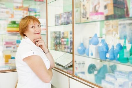 enema: Mature woman near counter in pharmacy drugstore Stock Photo