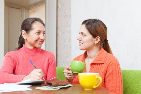 Adult daughter and mature mother is calculated the family budget at  home photo