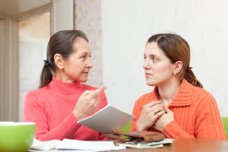 berate: Mature mother scolds adult daughter for payments bills or credits Stock Photo