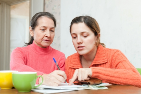 utility payments: adult daughter helps the mother to fills in  utility payments bills. Focus on mature Stock Photo
