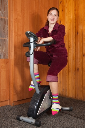 Woman exercise  indoors on a spinning bike photo
