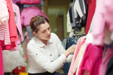 Female buyer  chooses children's clothes at clothing store photo