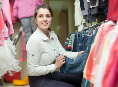 children's wear: Young mother  chooses jeans for her child at childrens wear store
