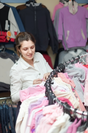 Female buyer chooses white blouse at clothing shop photo