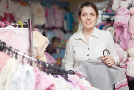 mother  chooses clothes for child at children's wear store Stock Photo - 17658802