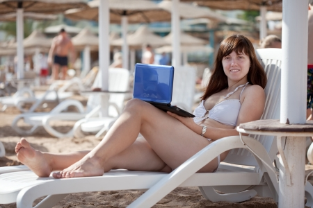 Happy  woman using  laptop at resort beach photo