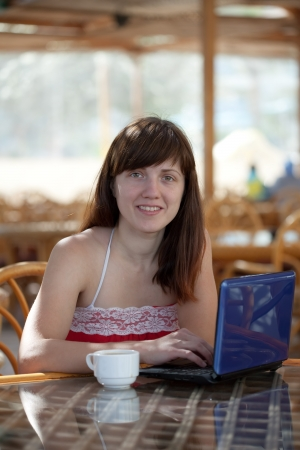 Happy  woman sitting  with laptop at resort cafe photo