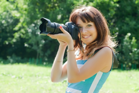 Young female photographer with camera outdoor photo