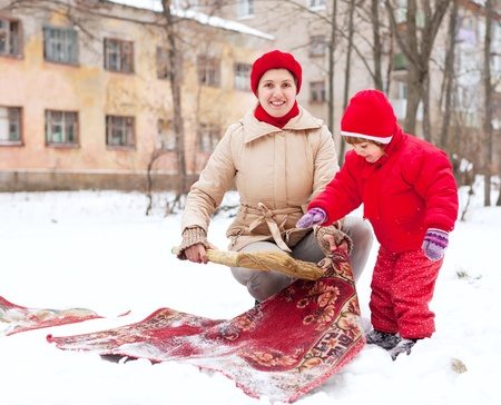 Smiling mother with child cleans rug with snow in winter day  photo
