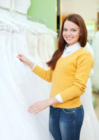 bridal salon: Smiling pretty woman  choosing white dress at shop of wedding fashion