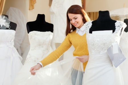 wedding gown: Smiling pretty woman shopping for wedding outfit in bridal boutique