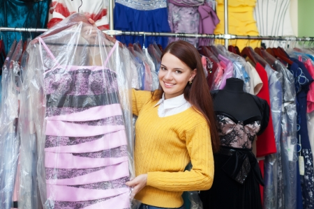 Girl chooses evening dress at clothing store photo