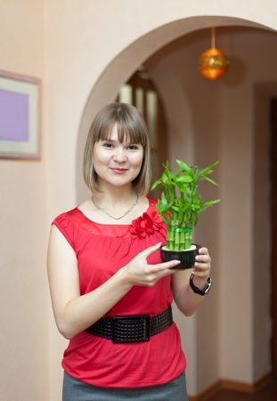 eastward: Girl with lucky bamboo plant at her home Stock Photo