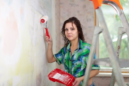 girl paints wall with roller at home photo