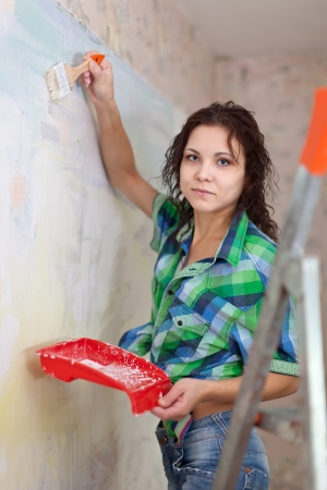 priming brush: woman paints wall with brush at home