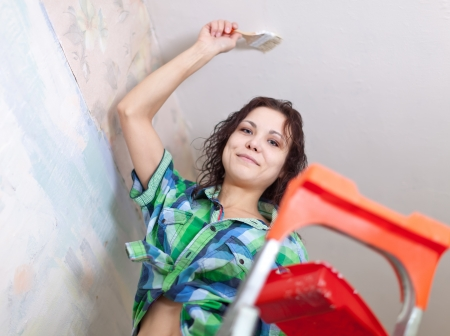 priming brush: Happy girl paints ceiling with brush at home