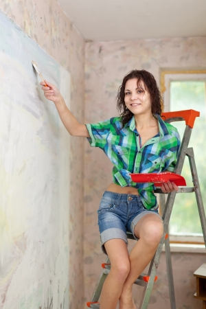 Happy girl paints wall with brush at home Stock Photo - 17744352