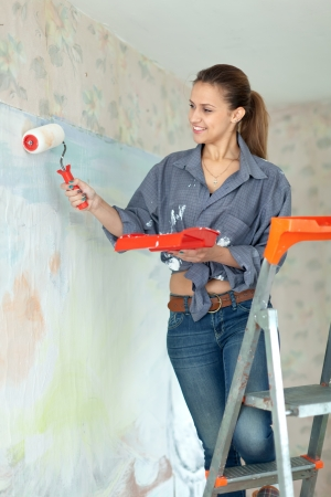 spalpeen: Happy woman paints wall with roller at home