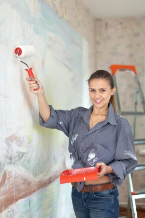 Happy woman paints wall with brush Stock Photo - 17767434